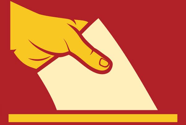 una mano che inserisce nell'urna una scheda