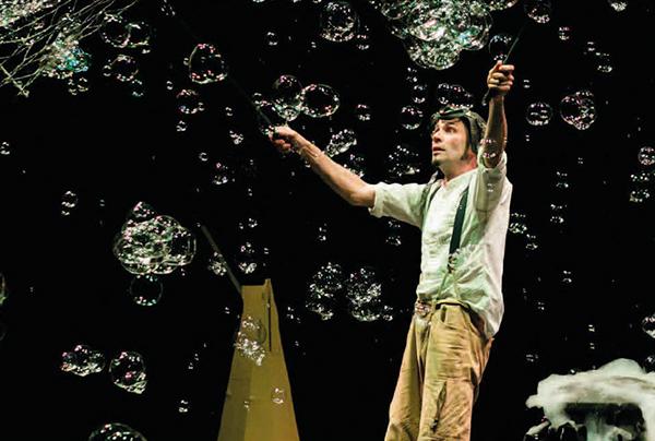 immagine di scena con l'attore Michele Cafaggi con grandi bolle di sapone