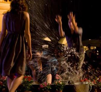 un uomo che schizza dell'acqua verso una ragazza