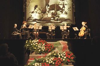 concerto al teatro alle vigne: la scalinata con fiori tricolori e i musicisti sul palco